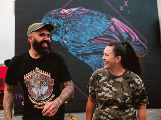 Charles and Janine Williams - Tāmaki Makaurau / Aotearoa 🇳🇿 @charles_phat1tmd @janine_divatmd . Thank you whanau for all you do and your tautoko towards our mahi and kaupapa 🙏🏽❤️ . Charles & Janine share a timely korero regarding their Art . 'Ka huhū te Hōkio, rorowhio ai aku taringa - the Hōkio whirrs', my ears whirr!' ~ Papa Manu (Kaumatua, Rangitāne Iwi) The majestic & now extinct Hōkioi (Haast Eagle) was carried by the uplift of the breeze from the sea up to the hills as it flew high above the valleys of Papaioea looking down for prey. The flapping of the wings created a whirr (the huuu huuu sound) & if that connected with your hearing (the rorowhio in your ears) it was a reminder that you were prey to its grasp & needed to keep a sharper eye on your actions in life.  It is a reminder for us all to have our ears tuned to the cry of the land & the people - to the efforts of strengthening the presence of mana whenua in the regions they whakapapa & connect to. Our solarised style reminds us that although it is extinct in the natural, the supernatural realm of its presence is with us always! Thank you to mana whenua, to Street Prints NZ/AU for having us in Papaioea (Palmerston North) & to everyone who put together such a great week. #birdgang #soularised #streetprints #streetprintspapaioea #charlesjaninewilliams . 📸 by @yoshi_travel_ . #bird #birds #nativebirds #maori #maoriartist #indigenous #indigenousart #indigenousartist