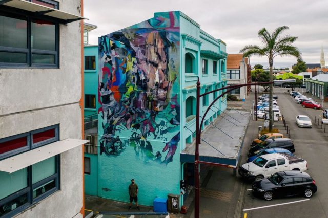 Askew One - New York / Auckland @askewone . Final mural for Street Prints Papaioea 2020. Located on King Street next to @ucolnz . Repost by Askew . So stoked to share my wall from @street_prints Papaioea. I got to indulge myself on this and created this 3 story mural that incorporated elements of my entire last years experiments. It has the layering of street texture with different blending modes shifting colours from positive to negative, it uses the glitch effects from the past years studies, it has the 3D scanned elements wrapped with street texture from the previous studies and it also incorporates a portrait component. I challenged myself to use as little spray paint as possible on this mural in keeping with some of the suggestions from my earlier post and was incredibly surprised with just how economical this all was. I ordered around 11 litres (2.75 gallons) of bucket paint and selected around six 1 litre (quarter gallon) pots from left over paint from the previous festivals to use. All up I'd be surprised if I put any more than 4 litres (1 gallon) on the surface all up! I used two spray cans for putting up the grid/sketching my design and about a quarter of a can putting some minor details on the mural. I did almost the entire thing with three brushes - only one needed to be thrown away by the end of the project. I mixed colours as I needed them on an old cardboard box as opposed to premixing them into pots and found this the most efficient process that created the least waste. I picked up these methods from a couple of different artists, firstly @sainer_etam and @bezt_etam who told me they often just ordered CMYK (Cyan, Magenta, Yellow and Black) plus white and a couple of pop colours ahead of festivals to keep their order simple. Secondly @smitheone from Mexico who I was working over from during the @muraloasis project. I was so impressed with his speed and efficiency/variety of colour produced by mixing on a palette versus premixing every colour needed. I also finally invested in a Graco cordless spray gun which I only used for the last touch, creating that fade into the background at the very bottom. #askew #askewone #post @resenecolour